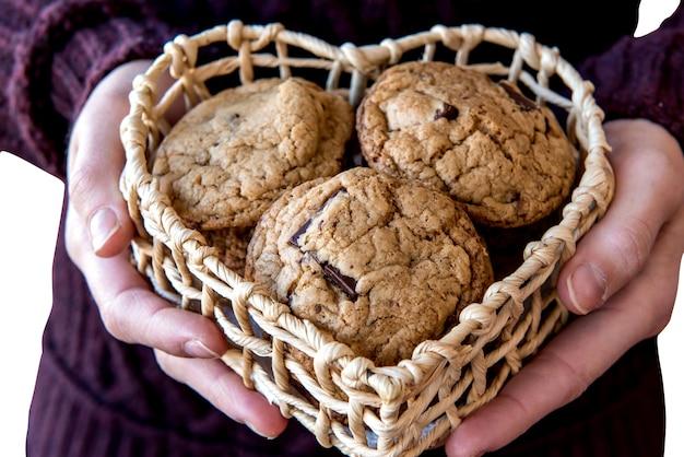 Fille tenant des biscuits au chocolat dans un panier coeur.