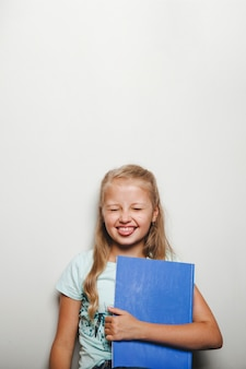 Fille tenant bloc-notes souriant