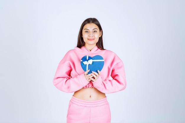 Fille tenant une boîte-cadeau en forme de coeur bleu et le démontrant