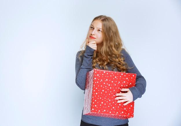 Fille tenant une boîte-cadeau rouge et semble confuse.
