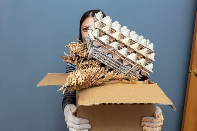 Fille tenant une boîte en carton avec du papier, des déchets de dessin animé, des ordures pour le recyclage