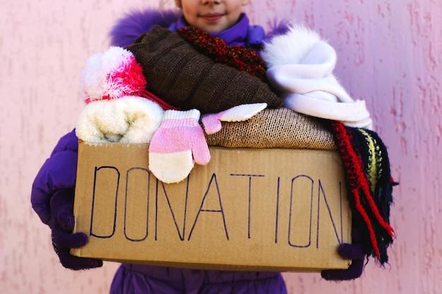 Fille tenant une boîte de dons avec des vêtements d'hiver chauds.