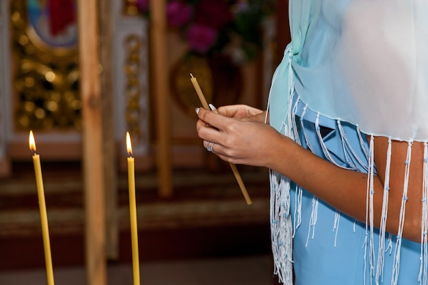 Fille tenant des bougies en cire. une bougie jaune a allumé le feu pour le culte. brûler des bougies en cire dans l'église