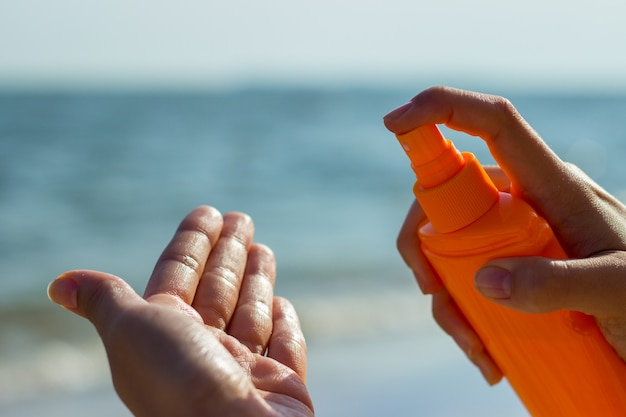 Une fille tenant une bouteille de crème solaire et appliquant la crème solaire sur la paume en vacances de plage tropicale