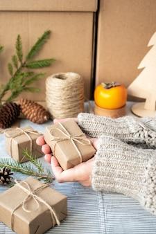 Fille tenant un cadeau emballé avec ses propres mains, gros plan. décoration de noël, conception d'un coffret cadeau pour noël en matériaux naturels. ambiance du nouvel an, préparation de noël.