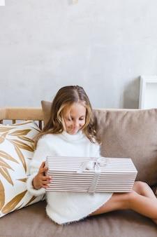 Fille tenant un cadeau, l'intérieur est décoré pour noël
