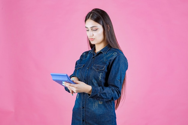 Fille tenant une calculatrice bleue dans la main et calcul