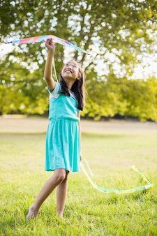 Fille tenant un cerf-volant dans le parc