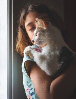 Fille tenant un chat de ruelle