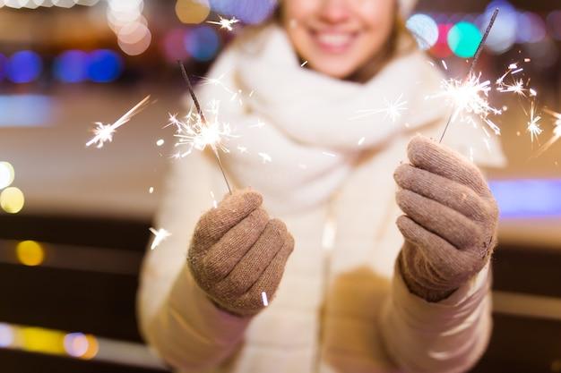 Fille tenant un cierge magique dans sa main en plein air hiver ville fond neige flocons de neige
