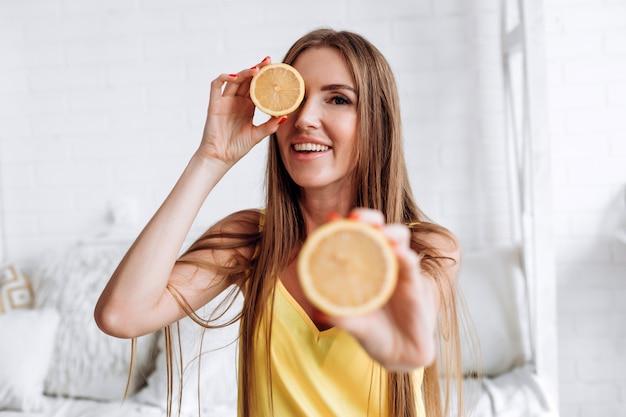 Fille tenant un citron dans sa main ferme ses yeux