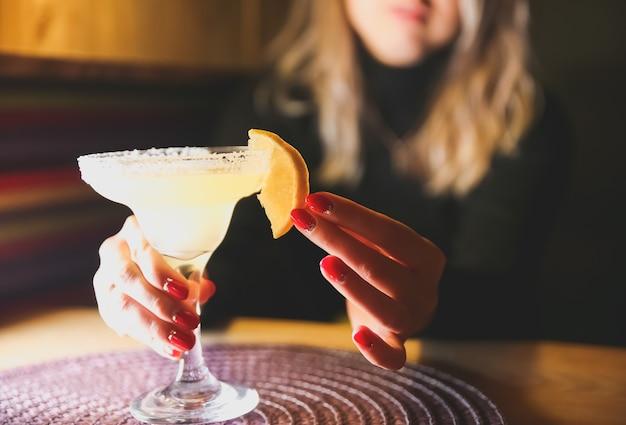 Fille tenant un cocktail margarita sur la table du restaurant. boissons alcoolisées. de belles mains.