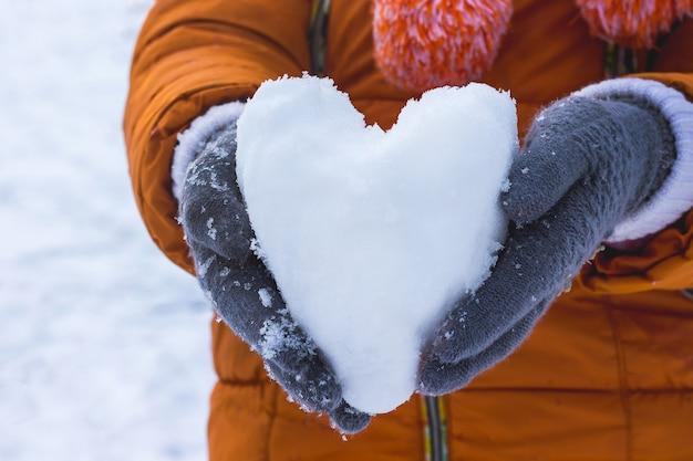 Fille tenant un cœur de neige, souhaite féliciter son amie pour la saint-valentin et lui souhaiter bonheur et amour