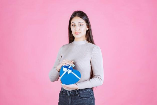 Fille tenant un coffret cadeau en forme de coeur bleu et le démontrant