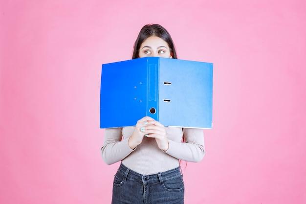 Fille tenant un dossier de projet bleu et cachant son visage derrière elle