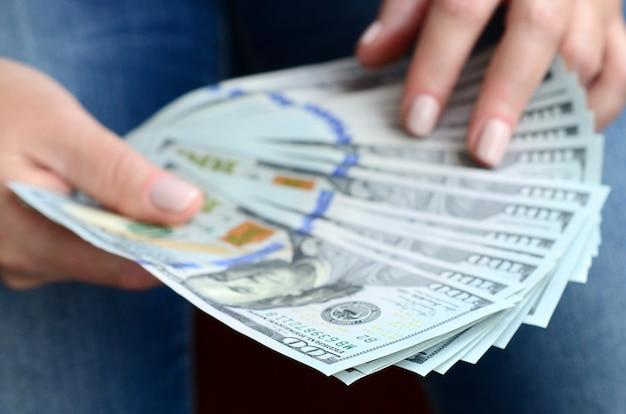 Une fille tenant un fan de billets d'un dollar