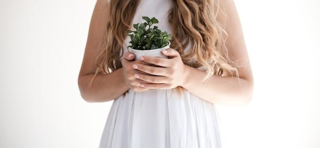 Fille tenant une fleur sur fond blanc.