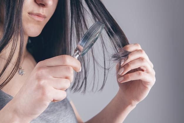 Fille tenant une loupe dans sa main et examine ses cheveux