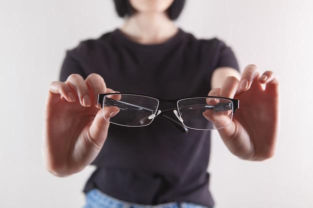 Fille tenant des lunettes à la main