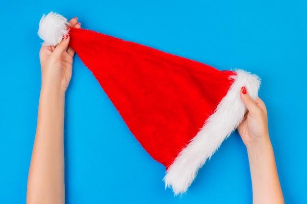 Fille tenant à la main un chapeau de père noël rouge sur la surface bleue