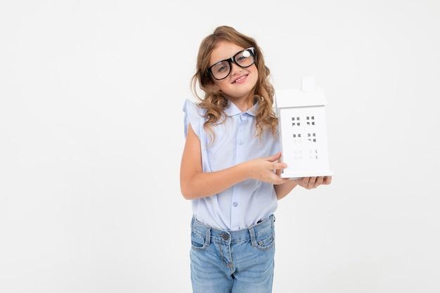 Fille tenant un modèle de maison en main avec espace copie