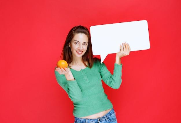 Fille tenant une orange fraîche et un panneau d'information rectangle.