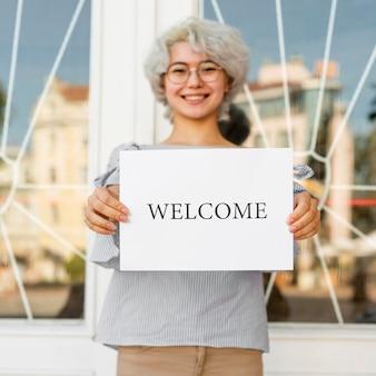 Fille tenant une pancarte de bienvenue