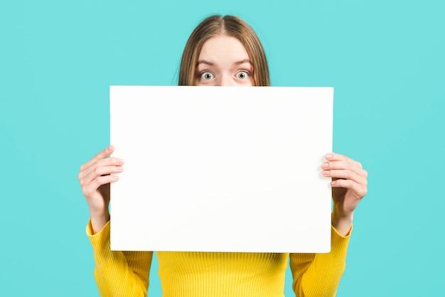 Fille tenant une pancarte blanche
