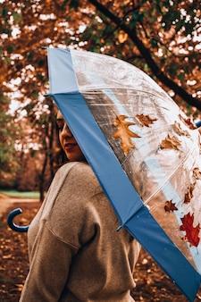 Fille tenant un parapluie transparent dans la rue d'automne en jour de pluie. femme sous parapluie transparent par temps de pluie. temps d'automne. feuilles sur parapluie