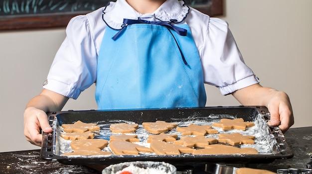 Fille tenant une plaque de cuisson avec des biscuits au gingembre fraîchement cuits