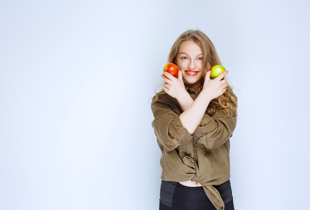 Fille tenant des pommes rouges et vertes dans les deux mains.