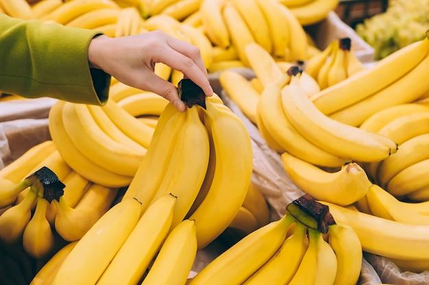 Fille tenant un régime de bananes dans le supermarché.