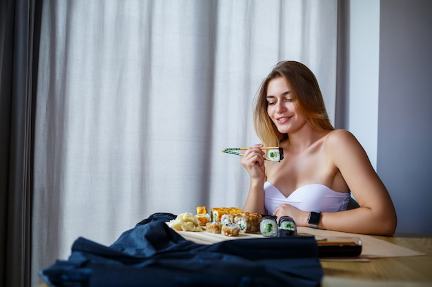 Fille tenant un rouleau de sushi de baguettes. jeune femme mangeant de délicieux sushis japonais frais.