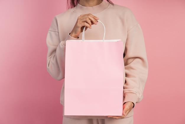 Fille tenant un sac en papier rose.