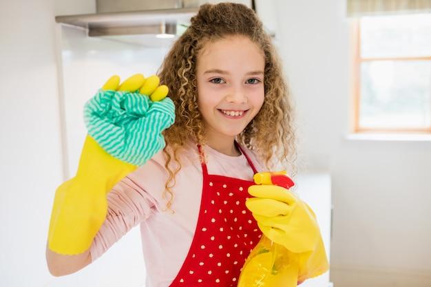 Fille tenant une serviette et vaporisateur dans la cuisine