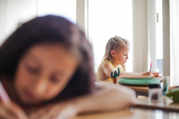 Fille tenant des stylos assis dans les bureaux de l'école