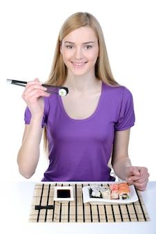 Fille tenant des sushis avec des baguettes et souriant.