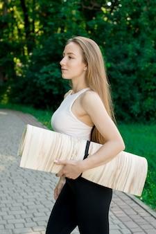 Fille tenant un tapis de yoga, elle va faire de l'exercice dans la nature
