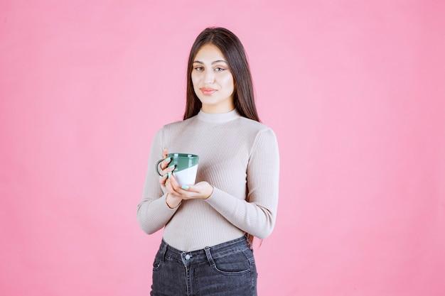 Fille tenant une tasse de café de couleur vert blanc et se sentir positif