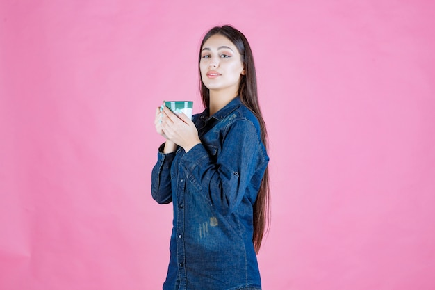 Fille tenant une tasse de café vert blanc et sentant