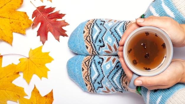 Fille tenant une tasse de thé dans ses mains dans des chaussettes chaudes, jour d'automne.