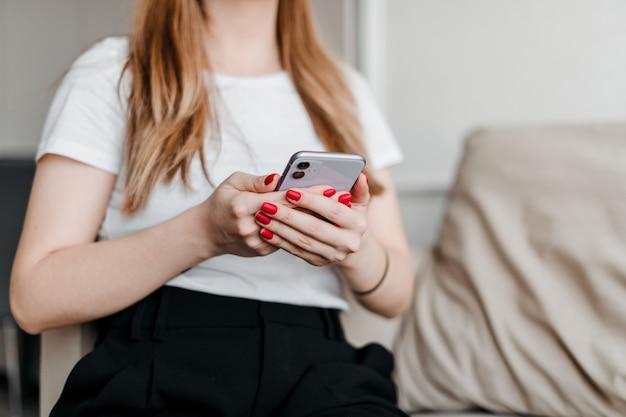 Fille tenant un téléphone assis sur un canapé dans un appartement moderne et lumineux