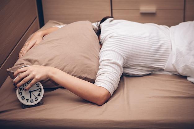 La fille tend la main au réveil.