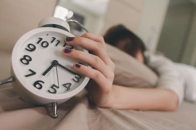 La fille tend la main pour couper le son d'un réveil blanc.