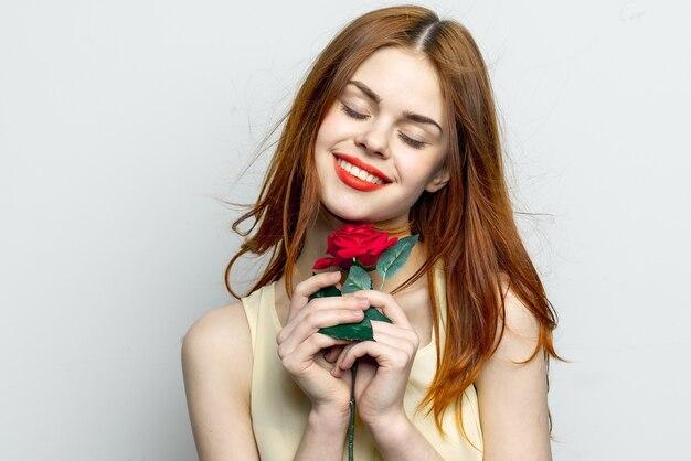 Fille tendre avec une fleur rose dans ses mains