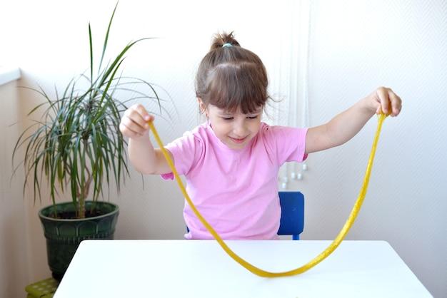 Fille tenir et étirer la boue jaune avec des tresses dorées sur une table blanche. enfant jouant avec un jouet visqueux. faire de la boue. espace de copie. notion de bricolage. temps pour expérimenter la méthode scientifique.