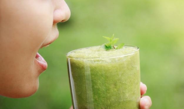 Fille tenir le jus de céleri dans un verre pour une alimentation saine avec des fibres