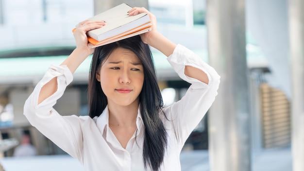 Fille tenir le livre sur la tête avec la pensée de sentiment