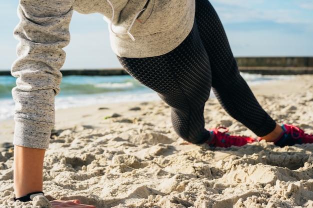 Fille en tenue de sport faisant des exercices sur la plage le matin