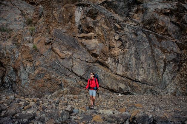 Fille en tenue de sport marchant avec sac à dos et bâtons de randonnée